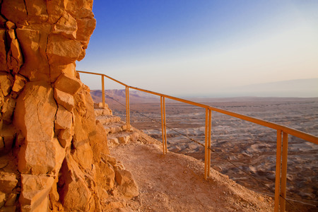 bannister: Limestone steep above desert with a safety bannister at sunset Stock Photo