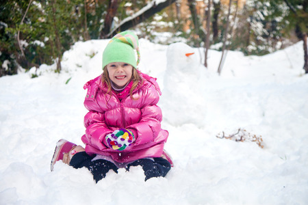 Cute blonde girl in Jerusalem making a snowball whie sitting in the snow in her house backyard photo