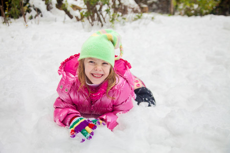 Laughing little girl making faces while playing in the snow at her backyard photo