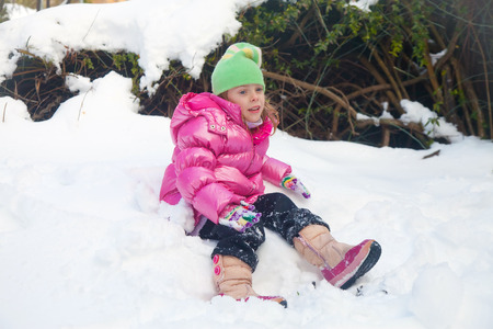 Cute blonde little girl sitting on the snow photo