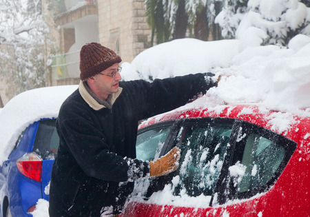 JERUSALEM - FEBRUARY 20: Man cleaning his car from the snow during a massive snowfall in Jerusalem on February 20, 2015