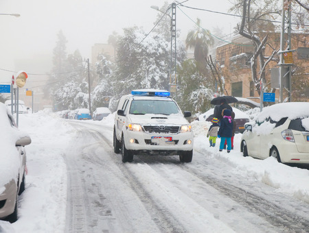 JERUSALEM - FEBRUARY 20: Police car patrolling the streets in the residential area of Jerusalem during a massive snowfall in Jerusalem on February 20, 2015 Editorial