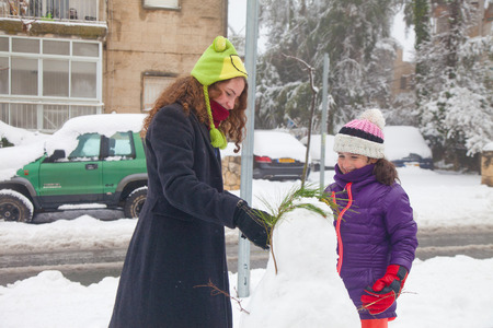 JERUSALEM - FEBRUARY 20: Young residents of Jerusalem building a snowman on the nearby street during a massive snowfall in Jerusalem on February 20, 2015 Editorial