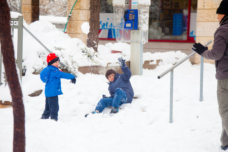 JERUSALEM - FEBRUARY 20: Father and sons playing snowballs joyfully after a massive snowfall in Jerusalem on February 20, 2015