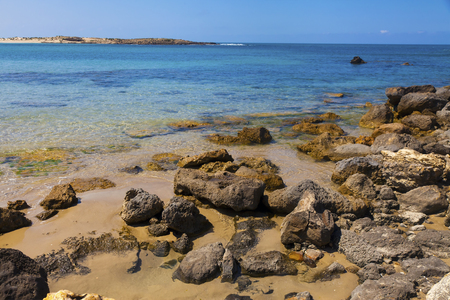 Water edge with large rocks on the sand and view of calm sea waters Stock Photo