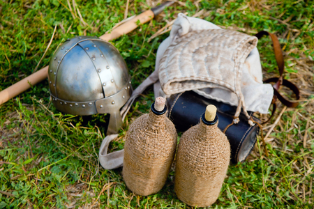 coif: Equipment of medieval traveling warrior - headwear, helmet, water flasks on the ground Stock Photo
