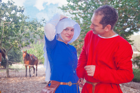 reenact: TSIPORI, ISRAEL - JULY 7, 2014: Young couple costumed as medieval civilians. Battle of Hattin history reenactment event of 2014. Battle of Hattin is the last battle of the Crusaders Kingdom of Jerusalem marking its fall in 1187.