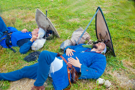 reenact: TSIPORI, ISRAEL - JULY 7, 2014: Two Crusader knights asleep before battle. Battle of Hattin history reenactment event of 2014. Battle of Hattin is the last battle of the Crusaders Kingdom of Jerusalem marking its fall in 1187.
