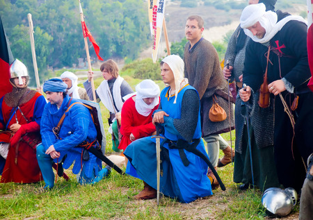 reenact: TSIPORI, ISRAEL - JULY 7, 2014: Crusarder warriors kneeled at prayer before march. Battle of Hattin history reenactment event of 2014. Battle of Hattin is the last battle of the Crusaders Kingdom of Jerusalem marking its fall in 1187.