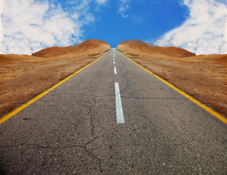 A fragment of old asphalt road between desert hills with symmetrical slopes before sunset