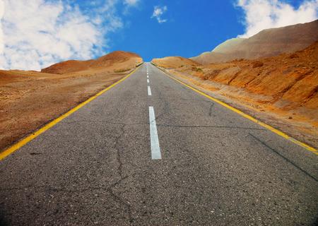 A fragment of old asphalt road between desert hills before sunset (with vignette effect)