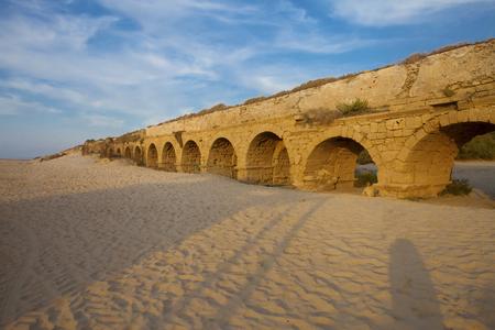caesarea: Golden-lit stones of Roman aqueduct in Caesarea at sunset (sunset lighting)