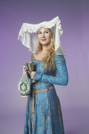 coif: Studio shot of beautiful girl dressed as a medieval noblewoman with a vase on purple background