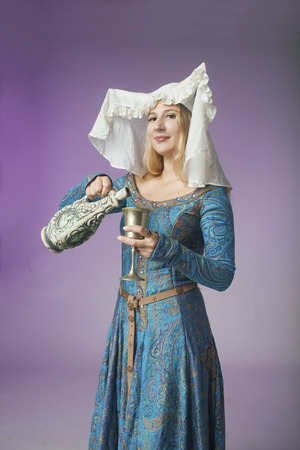 coif: Studio shot of beautiful girl dressed as a medieval lady pouring a drink on purple background