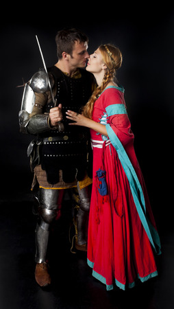 armor: Studio shot of young couple dressed as Medieval knight and maiden kissing over black background Stock Photo