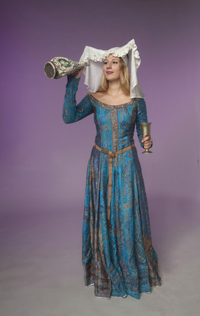 coif: Studio shot of beautiful girl dressed as medieval lady checking a jar for liquid