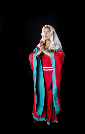 head scarf: Studio shot of beautiful girl dressed in medieval costume dress and head scarf praying over black background