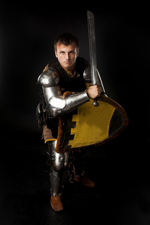 nobleman: Studio shot of young man dressed as medieval knight armed with sword and shield in defense position over black background Stock Photo
