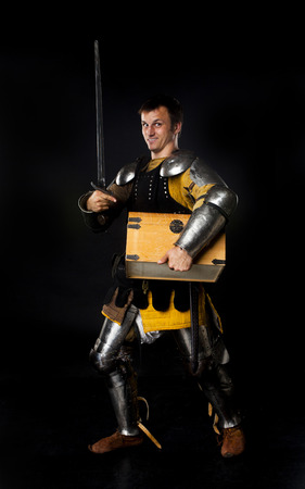crusade: Studio shot of young man dressed as medieval knight with a sword carrying a treasure chest Stock Photo