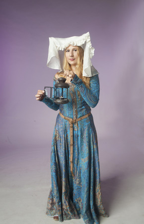 lady with the lamp: Studio shot of beautiful girl dressed as a medieval lady holding a retro style lamp on purple background