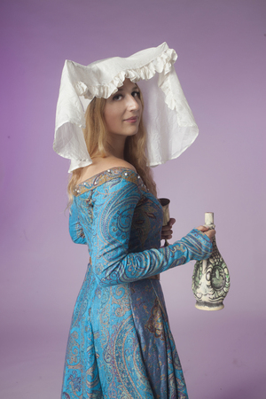 Studio shot of beautiful girl dressed as a medieval noblewoman half-turned holding a jar (on purple background) Stock Photo