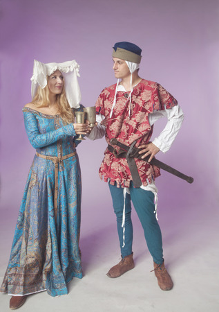 coif: Studio shot of young couple dressed in Medieval clothing toasting over purple background