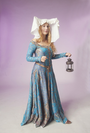 coif: Studio shot of beautiful girl dressed as a medieval noble lady holding a retro style lamp on purple background