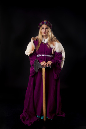 axe girl: Studio shot of beautiful girl dressed as a medieval noble lady in a mantle leaning on large axe (black background)