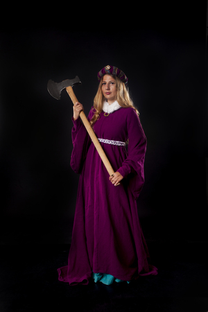 axe girl: Studio shot of beautiful girl dressed as a medieval noble lady in purple mantle with large axe on black background Stock Photo