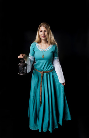 Studio shot of beautiful girl dressed in a medieval turquoise dress holding a retro style lamp on black background