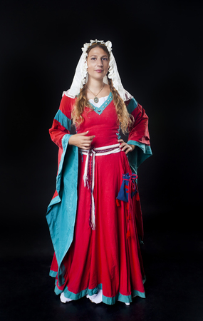lady in red: Front studio portrait of a girl dressed in medieval red dress and head scarf on black background