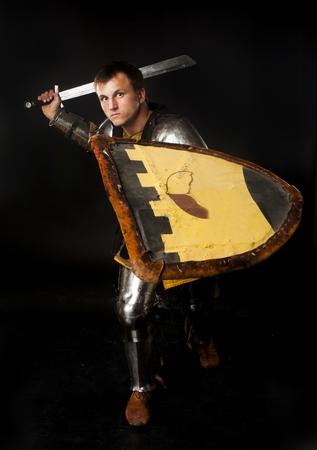 crucial: Studio shot of young man dressed as medieval knight swinging his sword for crucial attack