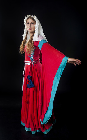 head scarf: Studio portrait of medieval girl in a red dress and head scarf on black background