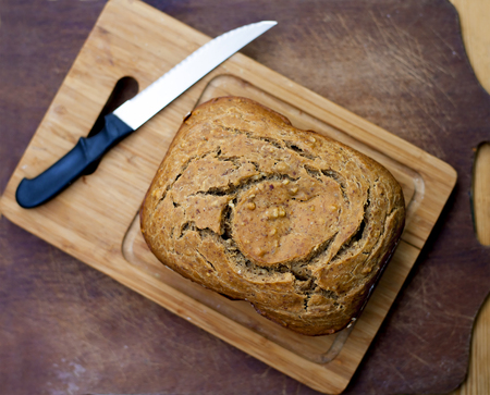 Fresh bread before serving on a wooden board with a simple knife out of DOF