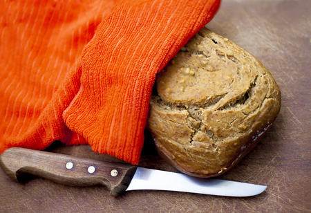 Fresh bread under a napkin and wood handle knife on a board