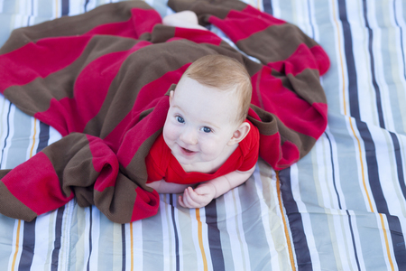 Cute laughing baby peeking from under daddys sweater