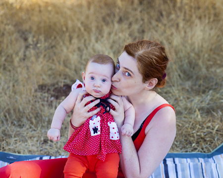 Portrait of a mother in a red dress with her baby daughter at sunset Stock Photo