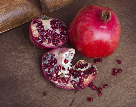 Ripe open pomegranate on wooden background