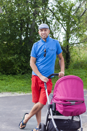 Handsome young man holding a baby stroller