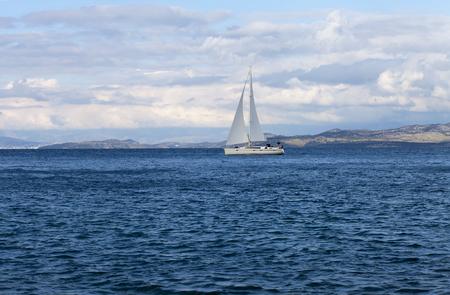 White yacht gliding through a blue bay Stock Photo