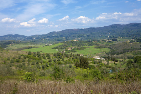 Beautiful cloudscape over Tuscan meadow and hill scenic