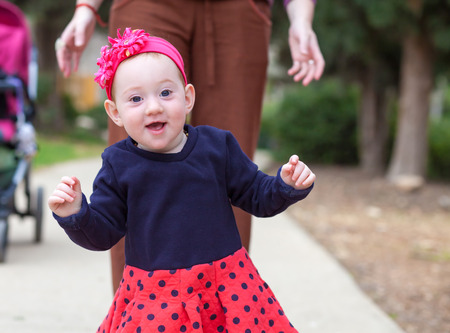 Adorable baby girl taking her first steps Stock Photo