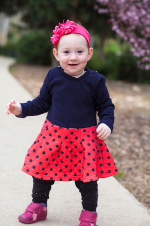 Portrait of cute baby girl standing on a park path Stock Photo