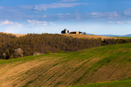 Beautiful Tuscan landscape with an isolated farmstead in the fields at sunset