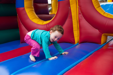 화려한 trampoline에 놀고있는 유아를 웃고
