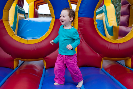 Funny laughing toddler runs on the trampoline