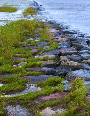 Natural breakwater dam shooting out into a lake with greens and water-worn boulders