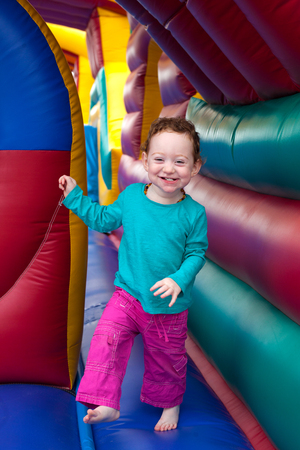Happy laughing redhead toddler bounce in a colorful trampoline Stock Photo
