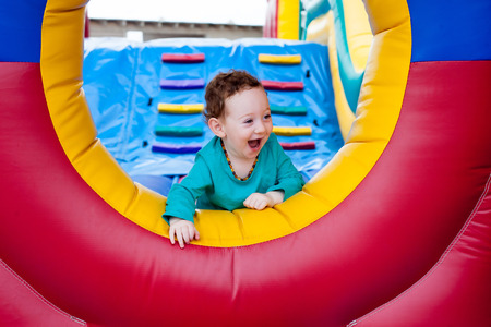 Happy laughing adorable toddler peeking out on trampoline Stock Photo