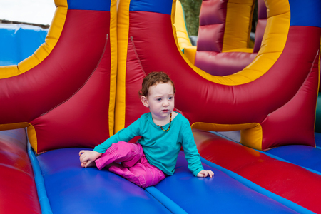 Toddler kid stopped to contemplate in the middle of a game of bounce on the trampoline Stock Photo